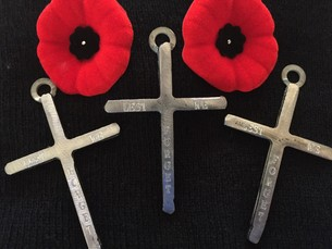 two poppy pins and three metal crosses